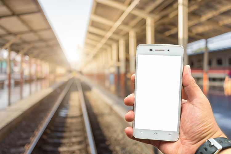 Communication Connection Focus On Foreground Hand Holding Human Body Part Human Hand Lifestyles Mobile Phone One Person Outdoors Portability Portable Information Device Rail Transportation Railroad Track Screen Smart Phone Technology Track Transportation Wireless Technology