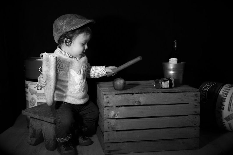 Cute boy holding bread and rolling pin by table against wall