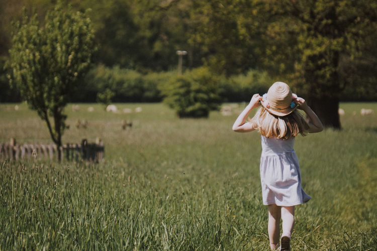 Young Girl running in a field Plant One Person Field Land Real People Grass Women Leisure Activity Nature Day Rear View Casual Clothing Lifestyles Standing Growth Hat Tree Three Quarter Length Adult Hairstyle Human Arm Outdoors Kid Kids Being Kids Girl
