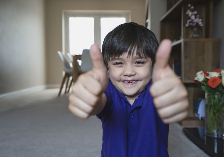 Portrait of smiling boy gesturing at home