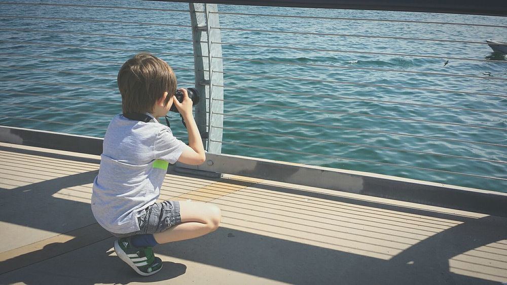 EyeEm Selects Childhood Outdoors People Child Lake Boy Camera Photographer Kneeling Boardwalk Rear View One Person Water Leisure Activity