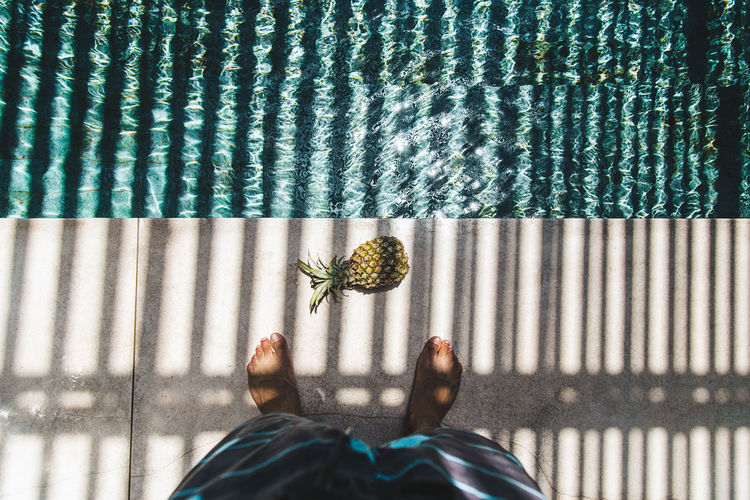 Low section of person standing by pineapple and swimming pool