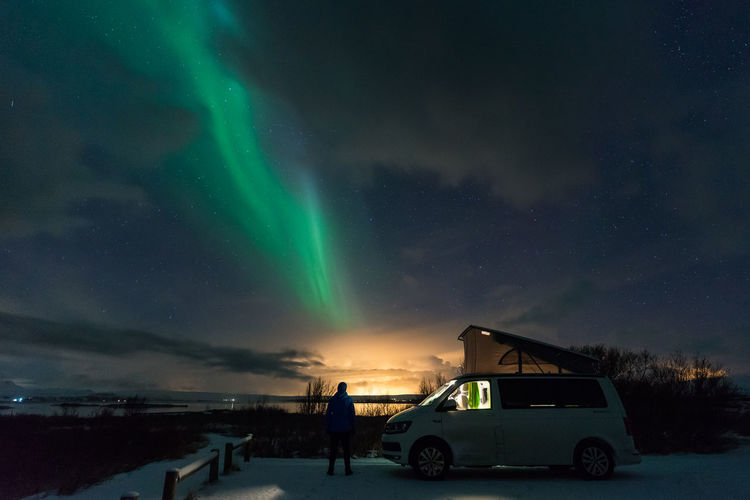 Cars on illuminated street against dramatic sky at night