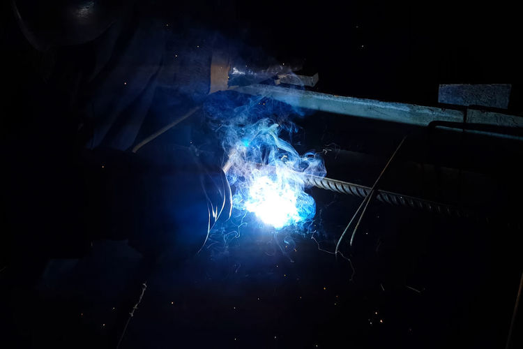 Indoors  Illuminated Smoke - Physical Structure Blue Night Light - Natural Phenomenon Sparks Welding Technology Motion Light Heat - Temperature No People Nature Burning Dark Blurred Motion Metal Industry