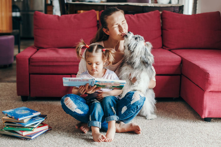 Mom reading book with baby girl toddler at home. funny home lifestyle family with licking pet dog.