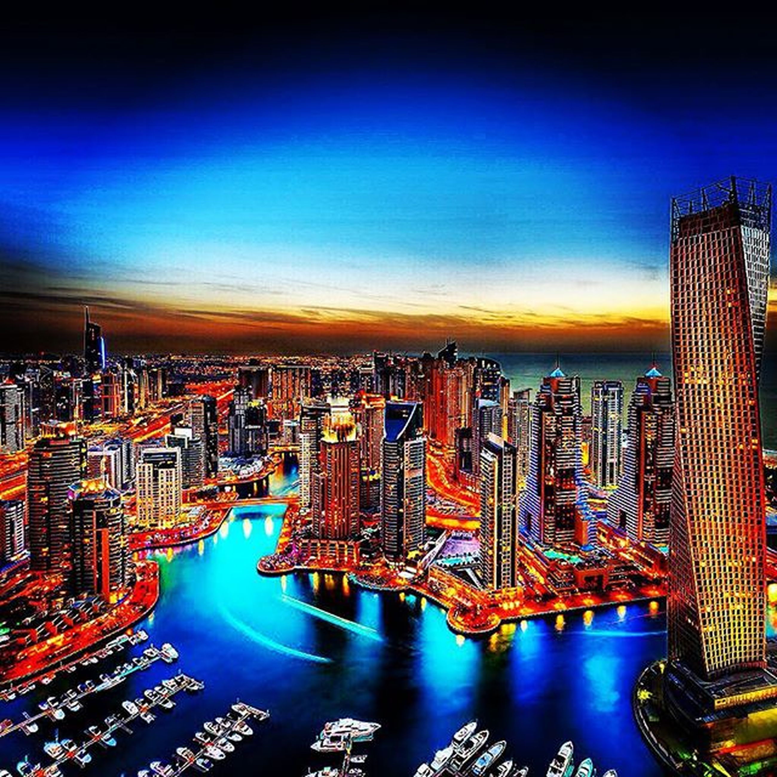 city, cityscape, architecture, skyscraper, building exterior, built structure, tall - high, tower, modern, illuminated, crowded, water, sky, office building, sunset, high angle view, capital cities, sea, financial district, urban skyline