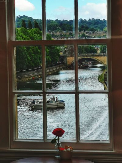 Boat sailing on canal seen through window