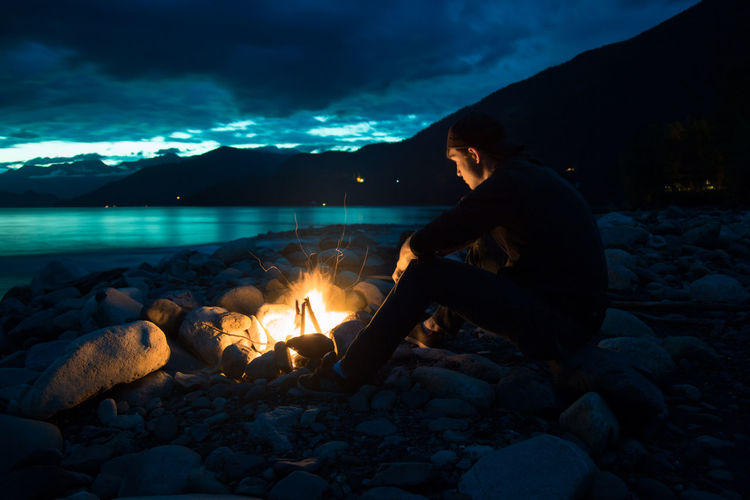 Lost in Thought Lost In Thought Campfire Fire Full Length Lake Landscape Leisure Activity Mountain Nature Outdoors People Real People Sitting Sky Slocan Lake Still Water Sunset Water