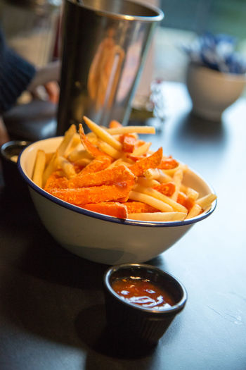 An enamelware bowl filled full of sweet potato fries and a side of sweet chilli dip. Fries Sweet Potato Fries Bowl Cafe Chips Deep Fried  DIP Enamelware Food Food And Drink Healthy Eating Prepared Potato Ready-to-eat Restaurant Table