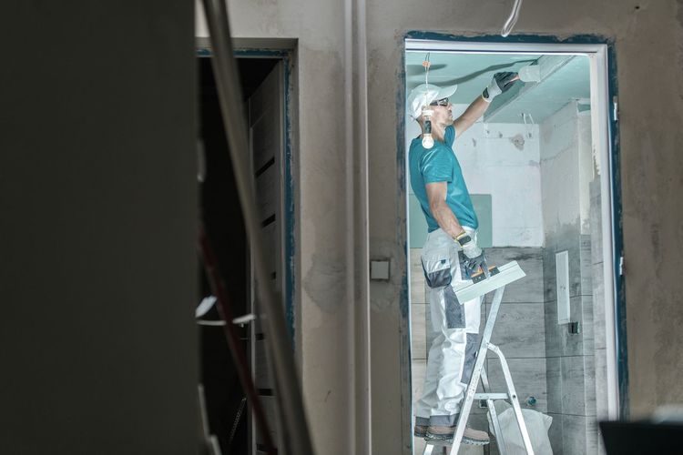 Side view of painter painting home