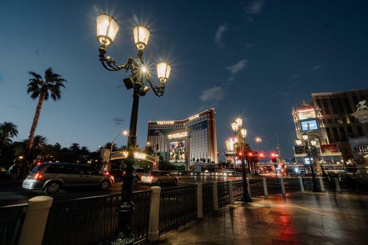 Illuminated city street against sky