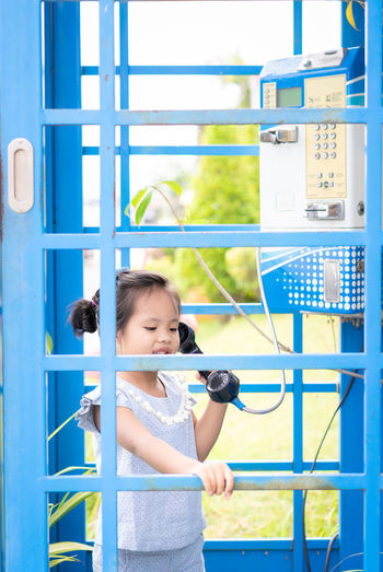 Cute girl talking on phone while standing in blue telephone booth