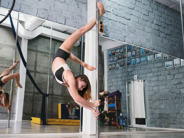 Sensuous woman practicing pole dance reflecting on mirror in studio