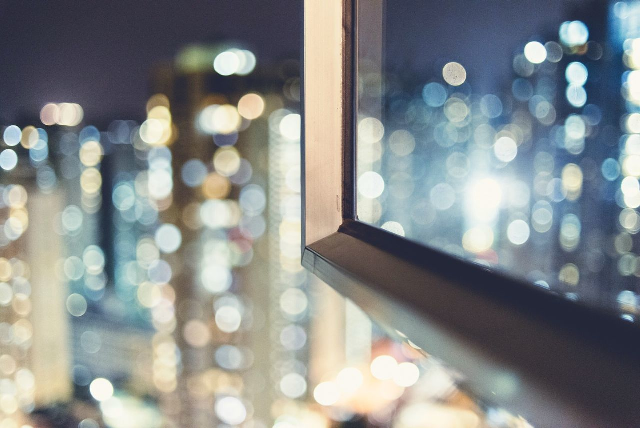 Defocused image of cityscape seen through window