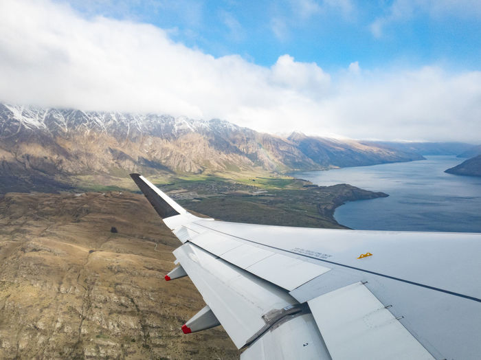 Looking at the hills around queenstown, new zealand over the wing of a plane.