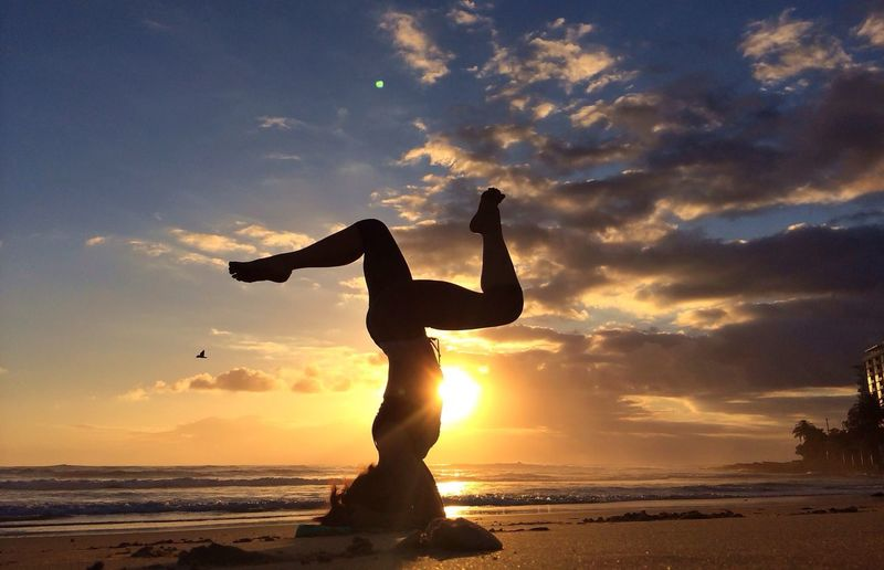 Side view of woman performing headstand on beach at sunset