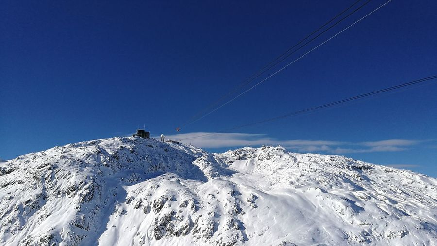 Low angle view of ski lift against blue sky