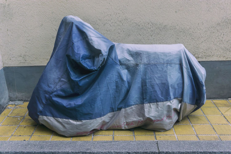 Motor scooter covered with tarpaulin on footpath by wall