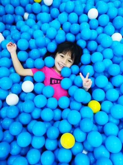 High angle view portrait of smiling girl wearing colorful balloons