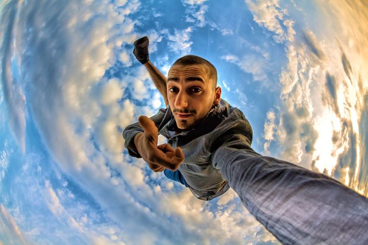 Fish-eye lens portrait of young man showing thumbs up amidst clouds