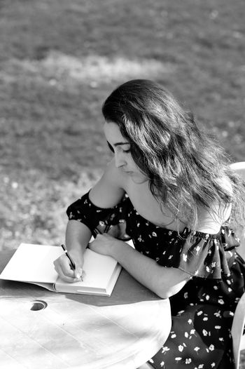 Young woman writing in diary at table while sitting outdoors