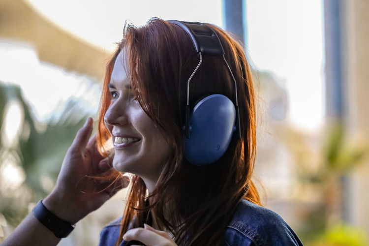 A young beautiful red-haired woman puts on antinoise headphones, preparing to fly a helicopter and, smiling, looks forward to the journey. Headshot One Person Music Headphones Listening Portrait Young Adult Happiness Young Women Lifestyles Leisure Activity Long Hair Real People Smiling Focus On Foreground Hairstyle Women Adult Hair Outdoors Beautiful Woman Red-haired Happy Happy People Joy Journey My Best Photo