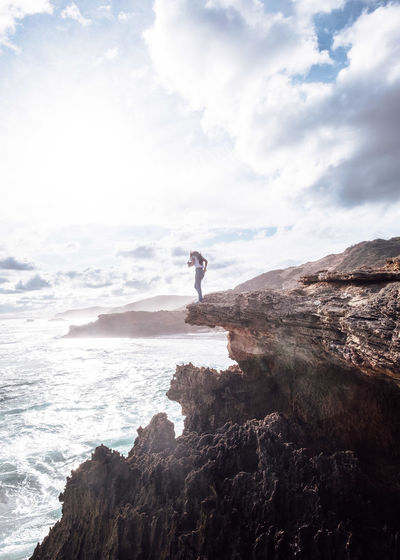 Man on cliff by sea against sky