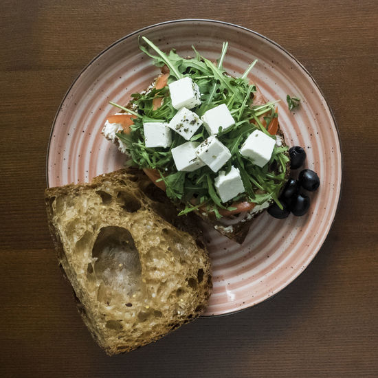 sandwich with feta cheese, tomatoes, olives, red onions and arugula Red Onions Sandwich Arugula Bowl Cheese Close-up Directly Above Feta Food Food And Drink Freshness Healthy Eating High Angle View Indoors  Leaf No People Olives Plate Ready-to-eat Table Tomatoes
