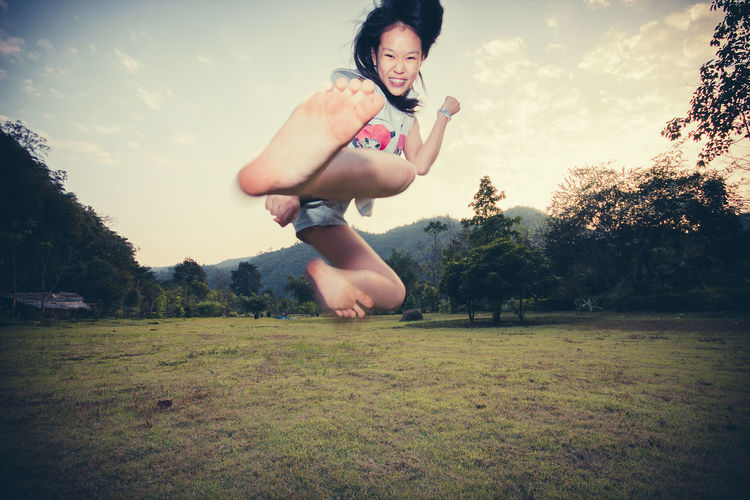 Portrait of woman kicking over field against sky