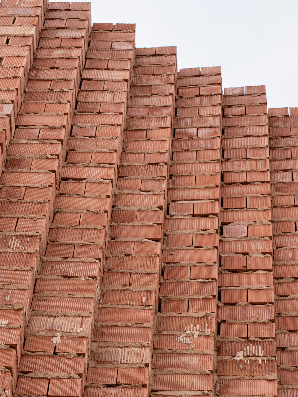 LOW ANGLE VIEW OF BRICK WALL AGAINST BUILDING