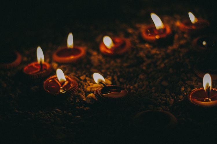 Close-up of illuminated diyas at temple
