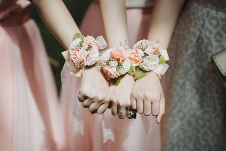 Midsection of bridesmaids showing flower bracelets in wedding ceremony