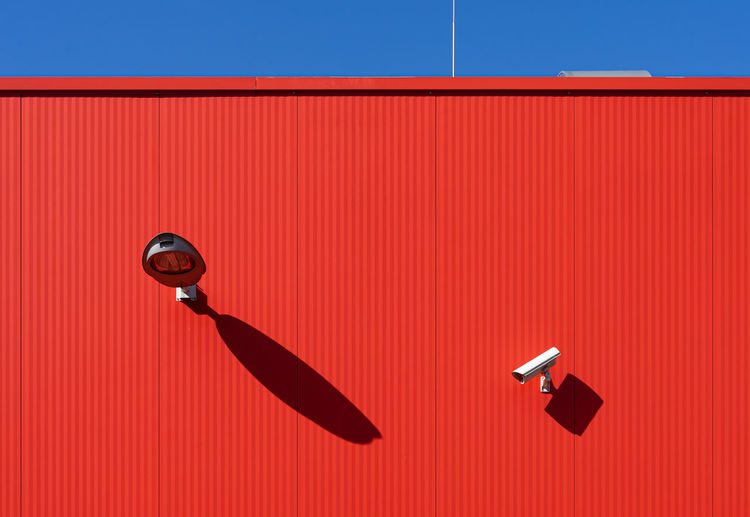 Security camera against red wall