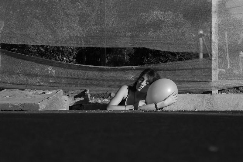Woman with balloon relaxing at construction site
