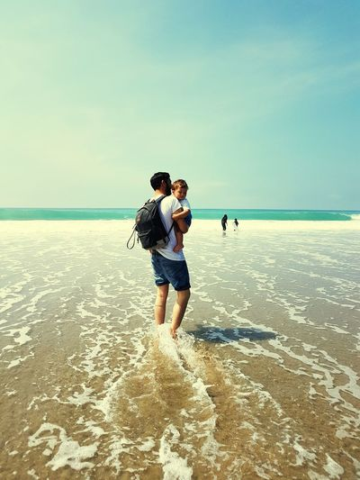 Young Man With Son Standing At Beach