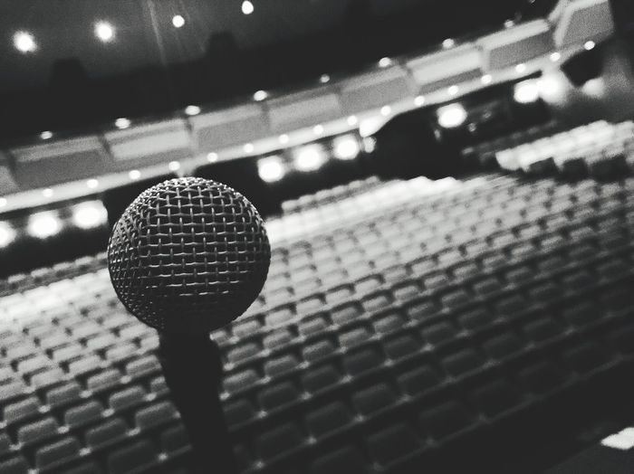 Tilt Shot Of Microphone Against Empty Seats In Auditorium