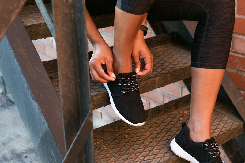 Low Section Of Woman Tying Shoelace On Metallic Steps