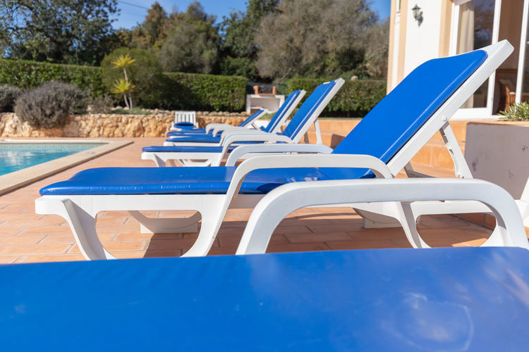 Chairs and table by swimming pool against blue sky