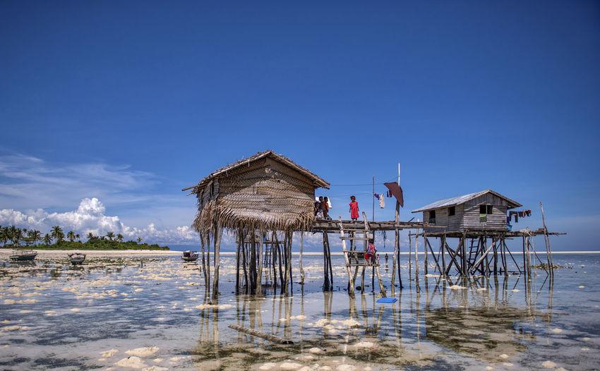 Lifeguard hut on beach by building against blue sky