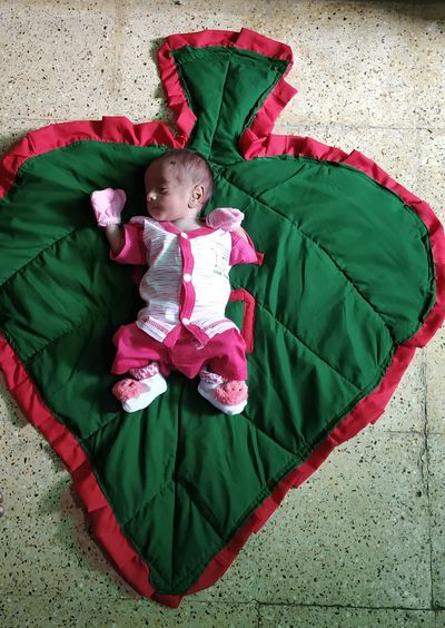 High angle view of baby girl lying on floor
