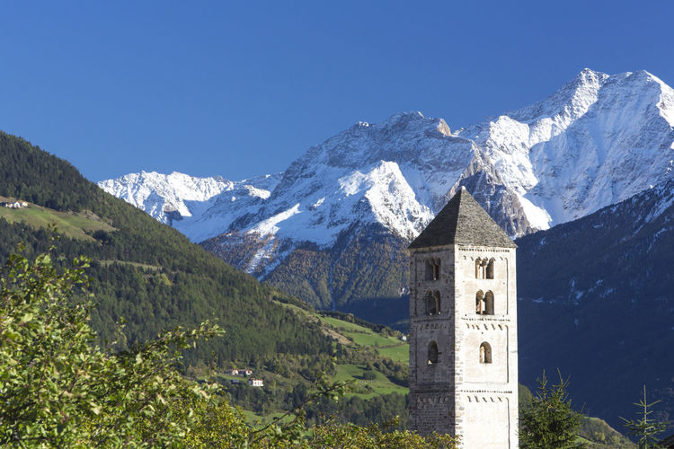 Italy, South Tyrol, Vinschgau, Mals, view to Fröhlichsturm church with alpine background Ancient Burgeis Church Holiday Maria Himmelfahrt Meran Ortler Reschensee Südtirol Alps Building Italy Mals Mountain Mountain Range Nature Romanic Snowcapped Mountain Springtime St. Benedikt Steeple Tower Venosta Vinschgau Winter