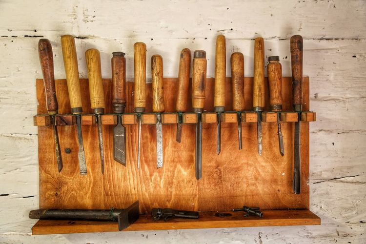 Close-up of chisels arranged on wooden shelf