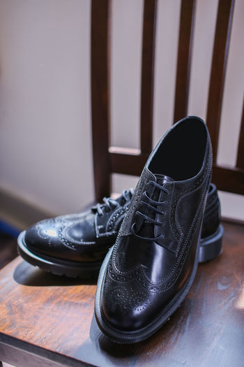 A pair of black leather shoes for the wedding day or working in the office. Elégance Wedding Black Color Brown Close-up Compatibility Day Dress Shoe Flooring Furniture Hardwood Floor Indoors  Lace - Fastener Leather No People Pair Personal Accessory Seat Shoe Shoelace Still Life Table Wood - Material