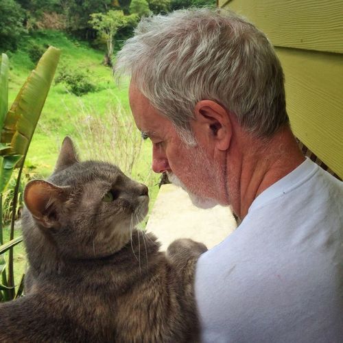 Close-Up Of Senior Man And Cat Looking At Each Other