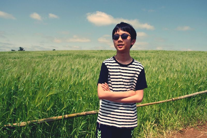 Portrait of teenage boy with arms crossed standing on field