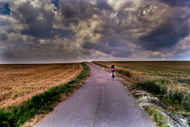 Person walking on road amidst field against sky