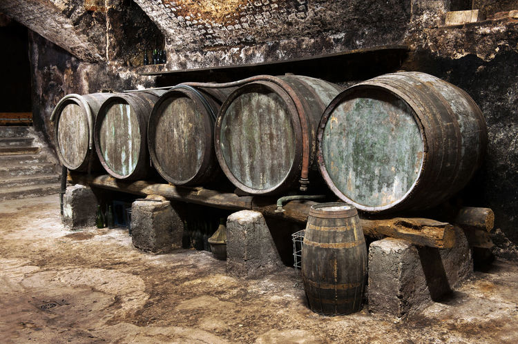 Row of old wooden oak barrels in a wine cellar on a winery for the production and maturing of local wines Beverage Casks Aging Alcohol Barrel Cellar Distillery Drink Fermentation Fermenting Grapes Maturing Oak Old Viticulture Wine Wine Cask Wine Cellar Wineglass Winemaking Winery Winery View Wooden