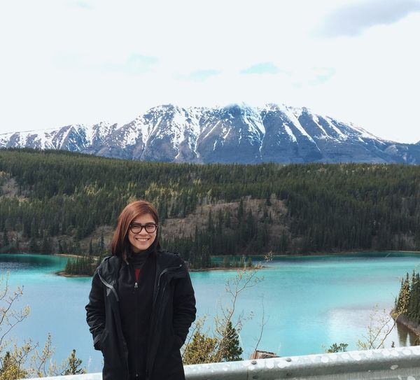 Portrait Of Beautiful Woman Standing In Front Of Lake Against Mountains During Winter