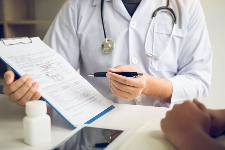 Midsection of doctor showing medical report to patient on table