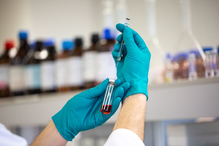 Cropped hand of scientist holding vial and syringe in laboratory